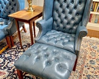 Blue leather tufted, hobnailed arm chairs and ottomans