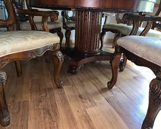 Round dining room table with six captain's chairs
