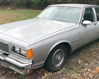 At 8PM: 1986 Chevy Caprice Classic Estate Auto, Brougham Edition; Gray Exterior with Burgundy Pinstripe Detail; Luxe Burgundy Velour Interior; Power Windows, Locks, Driver's Seat; AM/FM Radio with Cassette Player; Air Conditioning; V8 5.0L Engine. VIN: 1G1BN69H3GY106498 Vehicle Terms: - Vehicles are sold AS IS, in AS FOUND/ESTATE condition. - Minimum of 10% deposit due on day of auction (Cash, Check, VISA, MC, or Debit). - Balance paid in full by Thursday following (Cash or Certified Bank Check ONLY).