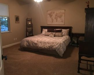 King size bed with Pottery Barn headboard and linens.  nightstand, bookshelf, armoire, dresser.