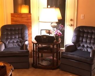 A pair of blue fabric swivel/rocking chairs