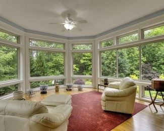 Sun room has leather furnishings and large rug.