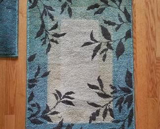 "Small area rug, 24"" x 36"".  Blues, beige, brown.  Leaves and branches pattern.  Made in USA.  Also, matching larger rug, 46"" x 64.5""."