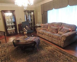 custom made couch matching wood and glass coffee table and end tables large muted color area rug 2 matching lighted china cabinets, crystal bell collection