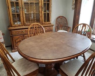 Beautiful oak dining room table and matching hutch, plus table cover, six chairs and leaf