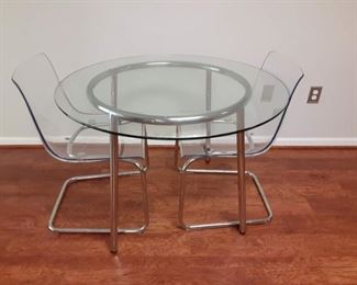 Round glass top and Chrome dining table with lucite and Chrome chairs