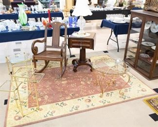 Several antique rocking chairs, book cases/shelves, lamps, and large area rugs.