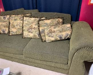 Large green sofa. Animal print reversible on the smaller pillows