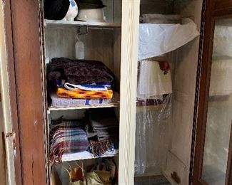 Interior of knock down wardrobe. Sheets, some vintage, hats, afghans, blankets