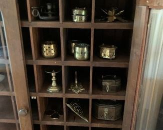 Brass collection in display cabinet