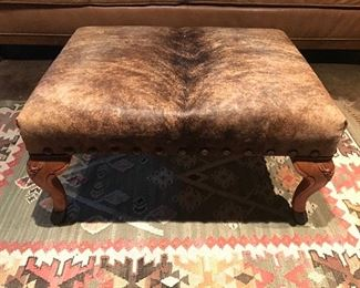 A cowhide ottoman that may just walk off.