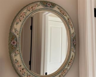 Round wall mirror with floral trim.