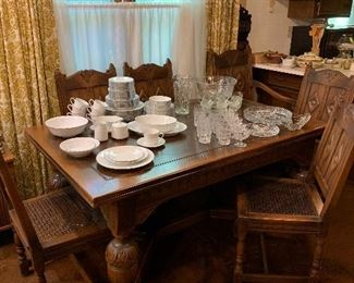 Beautiful Large carved wood dining table with 5 side chairs and 1 Captain chair. Seats are Cain. Table expands to twice its side with built in leafs! Also has table mats!