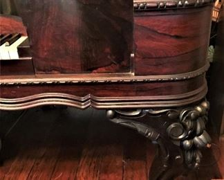 Detail on ornate moldings and legs on antique Rosewood Chickering Square Grand Piano