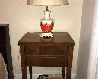 Vintage sewing machine in small cabinet, shown here being used as night stand.