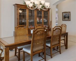 Gorgeous dining table and chairs and china cabinet in pristine condition. The table has an undelayment of rattan below the glass.