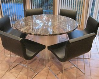 A set of six Ligne Roset Sala Chairs with a marble topped pedestal table.