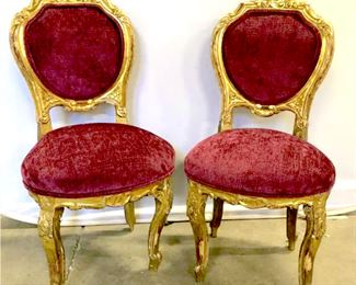 Pair Antique Possibly C 1860 Venetian Carved  Gilt Wood Chairs with cranberry toned  chenille upholstered seat and back cushion w  double welted trim. Measures approx 39 inches  tall x 19 inches wide x 22 inches deep, chips, cracks and wear to frame consistent  with age. Property of a former antique  dealer, description as per their appraisal.