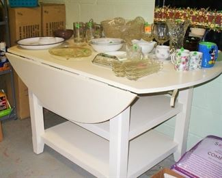 BRAND NEW DROP LEAF TABLE WITH SHELVING BELOW.  MATCHING CHAIRS NEW IN BOX TO THE LEFT OF PICTURE. NEVER USED