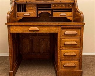 """Single pedestal roll top desk with S-curve tambour. Quarter sawn solid oak panels on sides, back, drawer fronts. Dimensions: 40"""" wide x 46"""" high x 30"""" deep. Dove-tail joinery on drawers. Easily dis-assembles to 3 pieces for transportation. Good condition for a desk approximately 75-100 years old."""