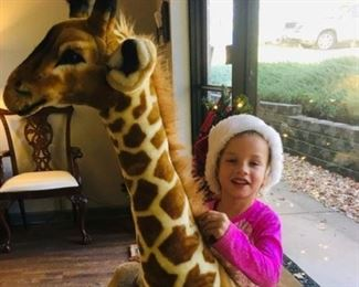 Mr. giraffe is tall enough for this cutie-pie to ride!