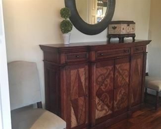 Buffet/sideboard, also makes an excellent bar. Shown with round beveled mirror, decorative chest and topiary