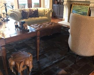 Overview of living room showing cow hide rug, custom sofa, elephant side table, and pair of tufted leather ottomans