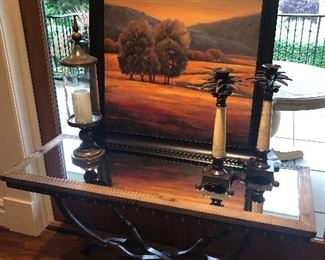 Wood and metal console table with mirror top, shown with palm tree candlesticks and framed print