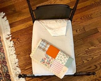 Vintage wooden cradle with quilt