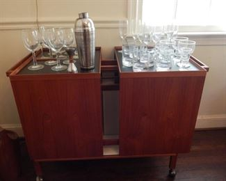 Mid Century bar on wheels. Really nice piece and it can be floated in the room because it is finished all around.
