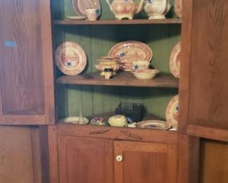 Painted interior of corner cupboard with red transferware teapots and plates