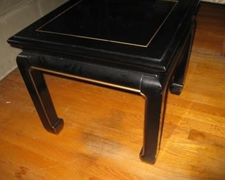 One of a pair of black laquer end tables