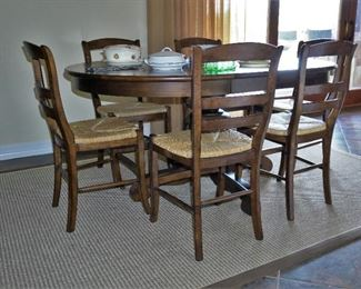 Dining table with single pedestal base and rush seat chairs