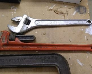 "Rigid 24"" pipe wrench, 18"" adjustable wrench. Many more of these in smaller sizes hanging on the walls along with more that 12 hammers, mostly unused"