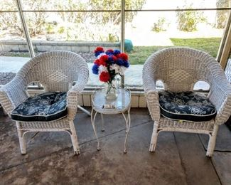 2 wicker chairs and a side Metal table