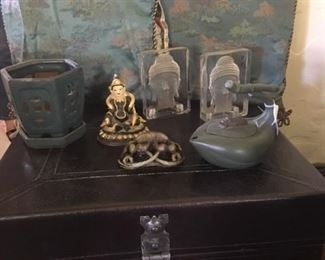 Chinese style black trunk end table, ceramic planter, glass Buddha bookends, silk throw pillows, tea pot, stone carving of a crab