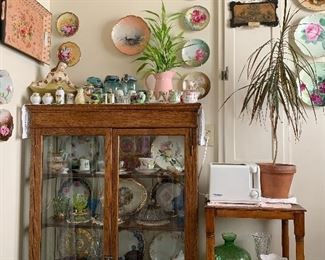 antique oak china cabinet/ display case, end table, floral plates, vintage salt and pepper shakers, antique glassware, metal trays