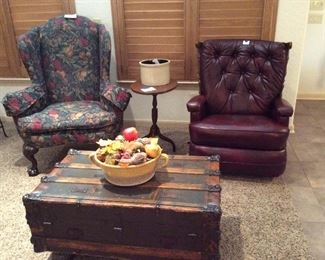 two cumfy chairs, one a leather recliner, and vintage trunk coffee table