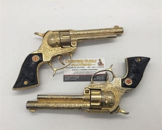 Lot 94 - Pair of RARE vintage Hubley gold tone Texan metal cap gun revolver pistols w/ black steer head