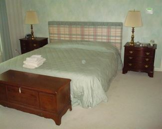 King bed with pair brass lamps and two bedside chests.