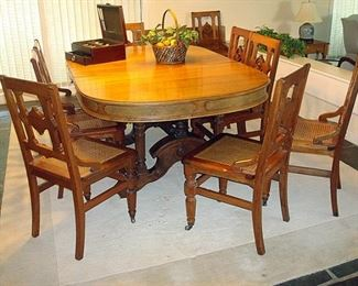 Antique Victorian Eastlake walnut dining table with several leaves and pads and nine walnut cane seat chairs. All from the period 1875.