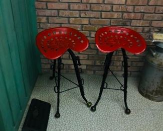 Pair of stools made from tractor seats and horse hames.