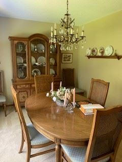 China cabinet and dining table with leaf and 6 cane-back upholstered chairs