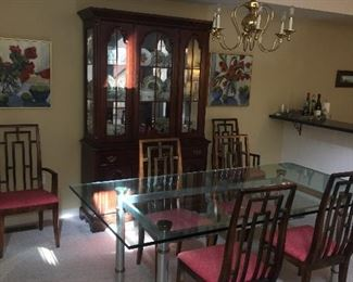 Nice glass, chrome, and brass mid century/Hollywood Regency dining table. Six chinoiserie style dining chairs.  Illuminated china cabinet by Broyhill.