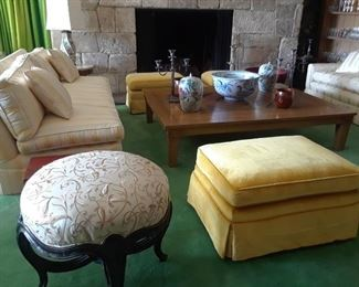 Silk embroidered puffed seat is  a showpiece. Huge coffee table is dramatic. Pair of sofas. Multiple footstools to pull up to the fire and conversation group.