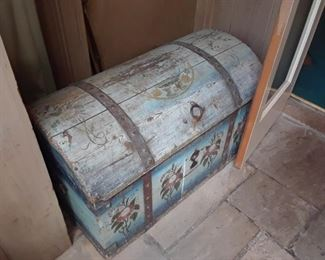 Antique hand painted hump back trunck, European. There are other similar antique pieces that will be under the tents on sale days.