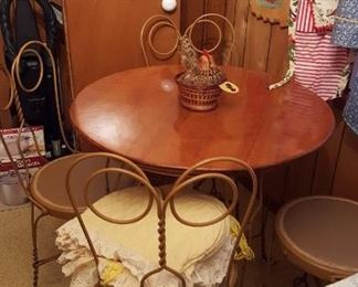 "Art Nouveau ice cream parlor table and chairs, in excellent condition from the early 20th century. The wrought iron ice cream parlor table and four chairs have a wooden tabletop. Classic ""spectacle"" curving and twisted design."