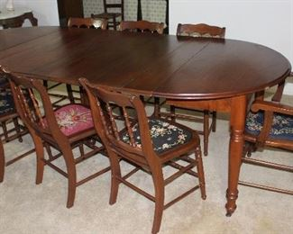 "Antique Round/Oval Table with 6 leaves on Turned legs and original Casters 94"" L x 45"" W x 30"" H shown with 8 (7 Side and 1 Arm) Chairs with various Floral needlepoint seat cushions"