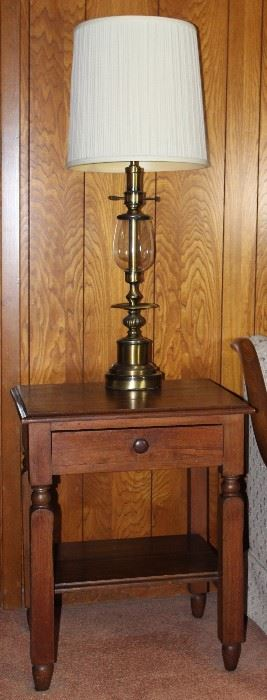 "Vintage end table with single drawer and lower shelf (22""W x 18""D x 26""H), shown with tall brass table lamp (1 of 2 shown)"