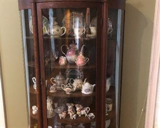 Really nice glass, curve-front cabinet filled with pretty porcelain nice for throwing at people